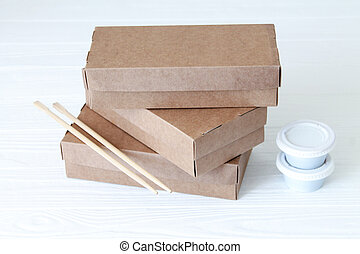 Healthy food sushi delivery in brown eco boxes. Close-up cases witn chopsticks and soy sauce boxes on white background