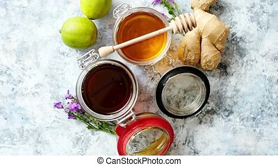Healthy food table with different kinds of honey, fresh ginger and lime
