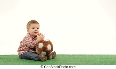 Healthy food - Young boy holding a soccer ball and eating an...