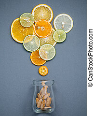 Healthy foods and medicine concept. Bottle of vitamin C and various citrus fruits. Citrus fruits sliced lime,orange and lemon on gray background flat lay.
