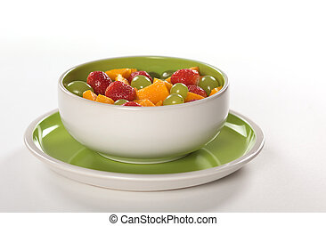 Healthy fresh fruit salad out of mango, strawberry and white grapes in green-white bowl photographed on white (Selective Focus, Focus on the middle)