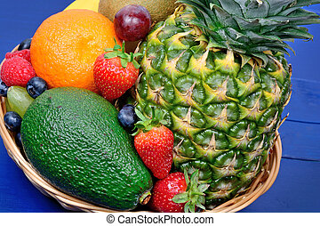 Healthy fresh fruits in a basket on wooden table
