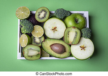 Healthy fruits and vegetables on a green table. Above view