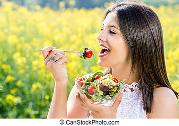 Healthy girl eating salad outdoors with flower field in background.