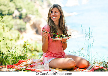 Healthy girl having salad at picnic.