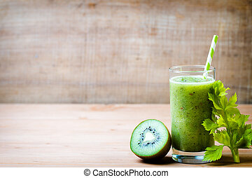 Healthy green smoothie in a glass on old wood.