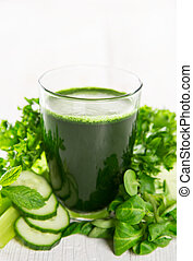 Healthy green smoothie in a glass with vegetables.