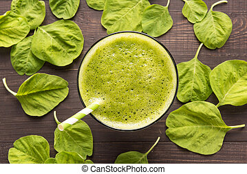Healthy green smoothie on rustic wood background.