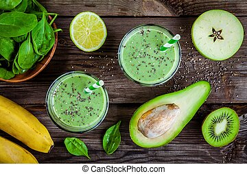 healthy green smoothie with banana, spinach, avocado and chia seeds in glass jars