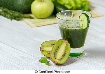 Healthy green smoothie with ingredients on white wooden background