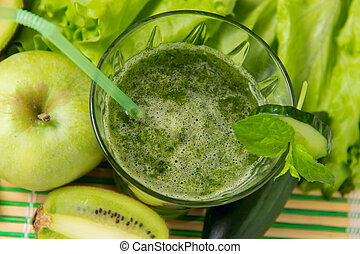 Healthy green smoothie with ingredients on wooden background