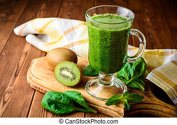 Healthy green smoothie with spinach and kiwi in glass on rustic wooden background.