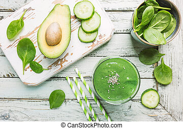 Healthy green smoothie with spinach, avocado, banana and chia seeds in glass jars on white wooden background, top view.