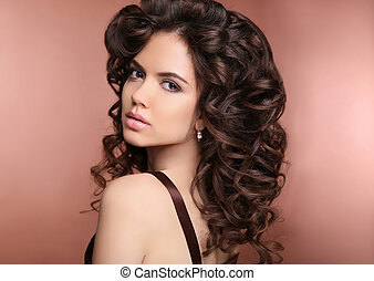 Healthy hair. Makeup. Beautiful brunette girl with long curly hairstyle. Elegant lady with jewelry.