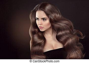 Healthy hair. Wavy hairstyle. Beautiful brunette woman model...