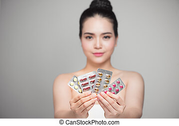 Healthy happy asian woman with pills in hand.