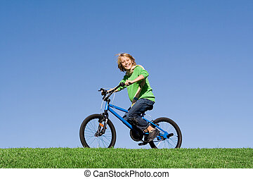 healthy happy kid playing outdoors riding bike