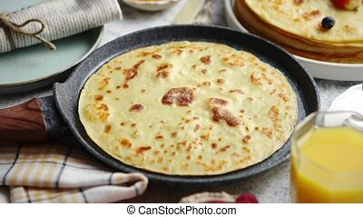 Healthy homemade pancake on stone frying pan placed on...