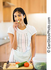 indian woman eating a slice of cucumber