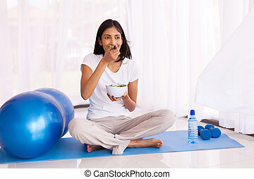 indian woman eating salad on exercise mat
