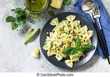 Healthy Italian cuisine. Pasta with green peas and pesto sauce in black bowl on grey stone background. Top view flat lay. Free space for your text.
