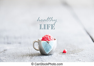 healthy life idea - text, raspberry and cup with a heart
