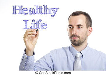 Healthy Life - Young businessman writing blue text on transparent surface