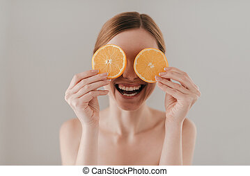 Healthy lifestyle. Attractive young woman holding orange slice and smiling while standing against background