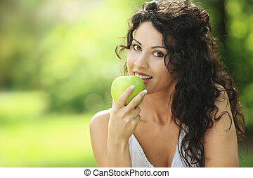 Healthy Lifestyle - Beautiful cheerful woman eating a green ...