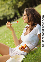 healthy lifestyle - Beautiful woman eating fruit salad on a ...