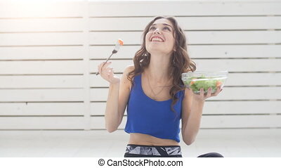 Healthy lifestyle concept. Smiling sporty young woman with green salad at home
