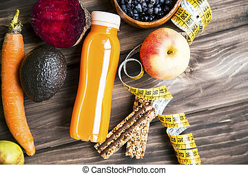 Healthy lifestyle concept with juice bottle, vegetables and fruits with granola muesli bars and measuring tape on wooden board, top view, healthy living fitness concept