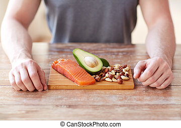 close up of male hands with food rich in protein - healthy ...