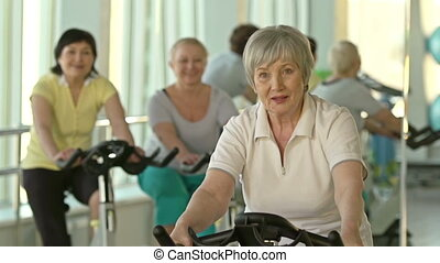 Healthy Lifestyle - Focus on elderly woman cycling in gym