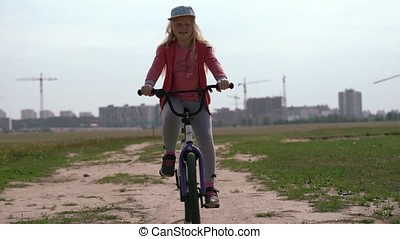 healthy lifestyle - girl riding a bicycle across the field near the city