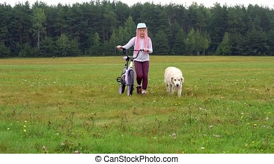 healthy lifestyle - girl with a bicycle and a dog walking on a field near the city