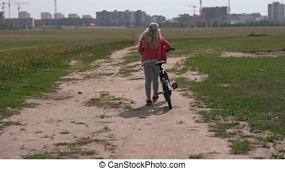 healthy lifestyle - girl with a bicycle walking on a field near the city