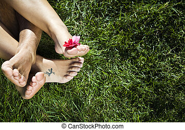 Healthy lifestyle: young couple laying down on the grass