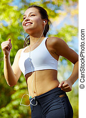 Healthy lifestyle - Portrait of a young woman jogging with a...