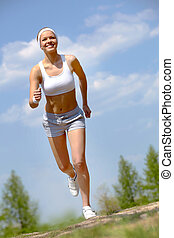 Portrait of happy young woman jogging outside