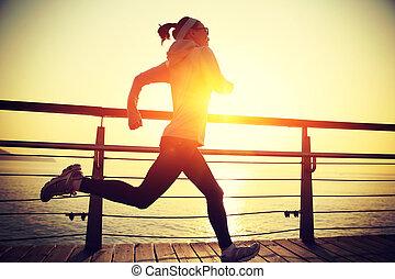 woman running on wooden boardwalk