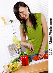 Stock image of woman in kitchen preparing a fresh vegetable salad