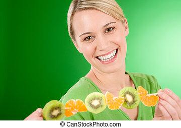 Healthy lifestyle - woman eating kiwi and orange on stick