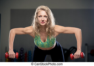 healthy lifestyle, woman exercising with dumbbells in the gym