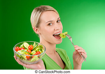 Healthy lifestyle - woman holding vegetable salad on green ...