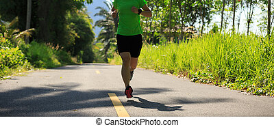 healthy lifestyle woman running at morning tropical forest trail
