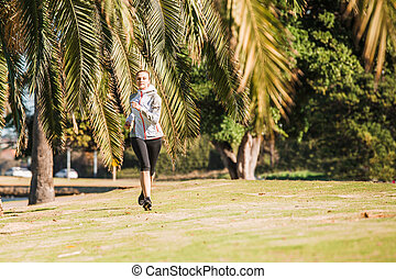 Healthy lifestyle young sporty woman jogging at tropical park along palm trees