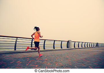 healthy lifestyle young woman runner running at seaside