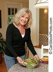A beautiful, mature woman serving a healthy green salad.