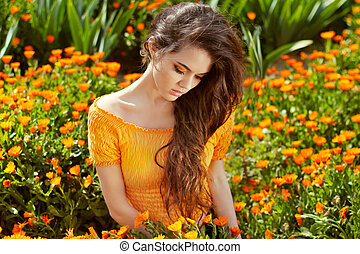 Healthy Long Curly Hair. Beautiful Brunette Woman over marigold flowers, outdoors portrait